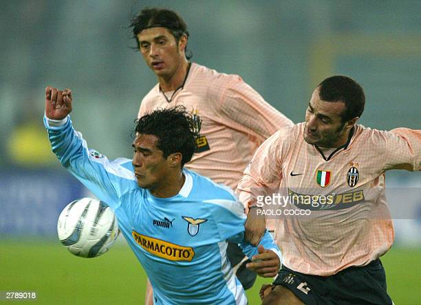Lazio striker Bernardo Corradi is tackled by Juventus players Paolo Montero and Alessio Tacchinardi during their Serie A soccer match at Rome's...
