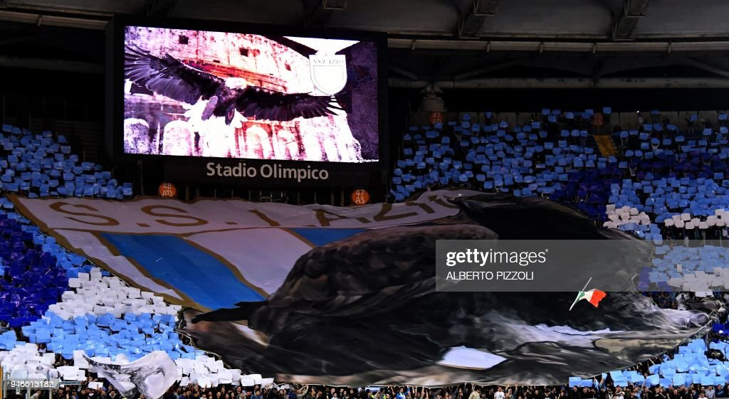 Lazio supporters display their team's logo on a giant banner during the Italian Serie A football match between Lazio and Roma on April 15, 2018 at Olympic Stadium in Rome. /