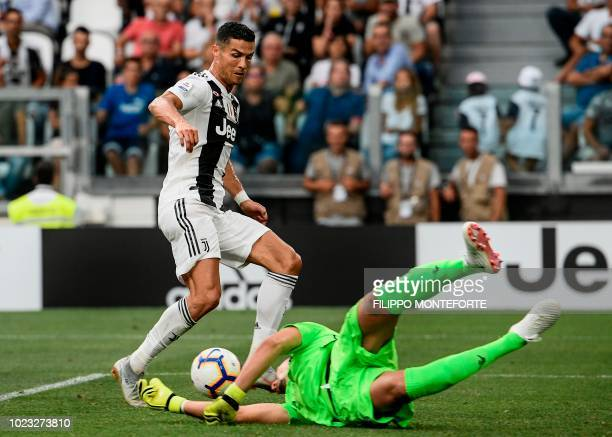 Lazio's Albanian goalkeeper Thomas Strakosha defends against Juventus' Portuguese forward Cristiano Ronaldo during the Italian Serie A football match...