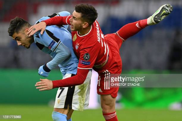 Lazio's Brazilian midfielder Andreas Pereira and Bayern Munich's French defender Lucas Hernandez vie during the UEFA Champions League Last-16, second...