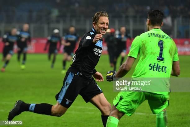 Lazio's Brazilian midfielder Lucas Leiva celebrates with Lazio's Albanian goalkeeper Thomas Strakosha after scoring the winning penalty during the...