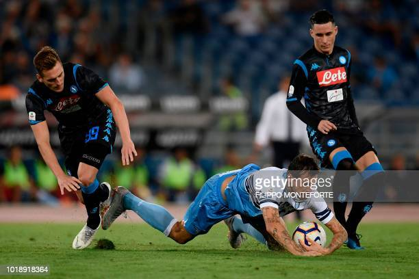Lazio's defender Francesco Acerbi falls on the ball after challenging with Napoli's Polish forward Arkadiusz Milik during the Italian Serie A...