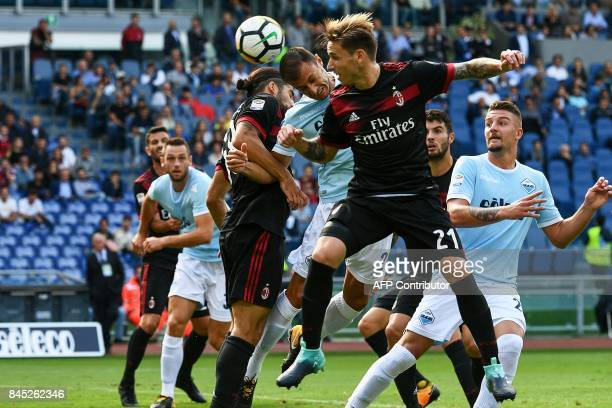 TOPSHOT Lazio's defender from Romania Stefan Radu heads the ball between AC Milan's midfielder from Argentina Lucas Biglia and AC Milan's defender...