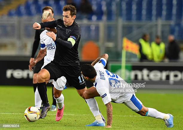 Lazio's forward from Germany Miroslav Klose vies with Dnipropetrovsk's forward from Brazil Matheus during the UEFA Europa League football match...