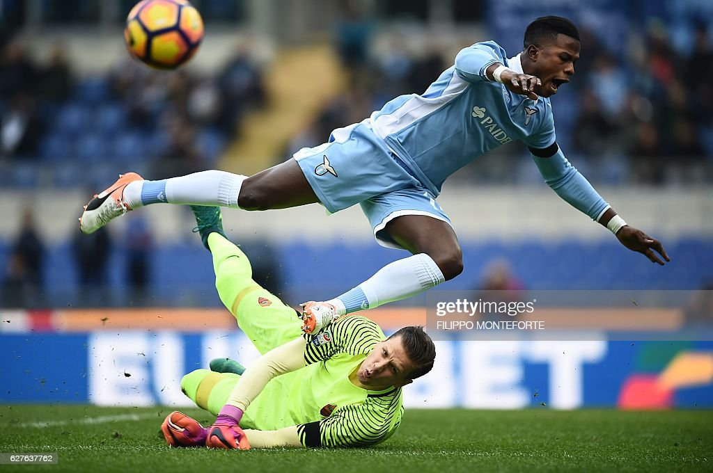 TOPSHOT - Lazio's forward from Senegal Balde Diao Keita (top) tries to score against Roma's goalkeeper from Poland Wojciech Szcz?sny during the Italian Serie A football match SS Lazio vs AS Roma on December 4, 2016 at the Olympic stadium in Rome. / AFP / FILIPPO