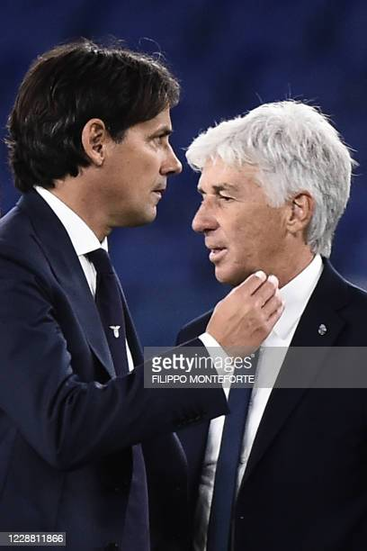 Lazio's Italian coach Simone Inzaghi and Atalanta's Italian coach Gian Piero Gasperini pass each other on the pitch at the end of the Italian Serie A...