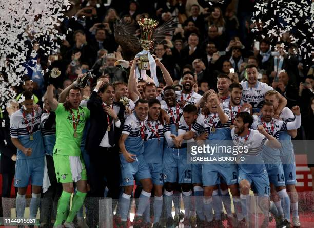 Lazio's Italian coach Simone Inzaghi and his team players celebrate as they hold the Tim Cup trophy with their mascot eagle on the background during...