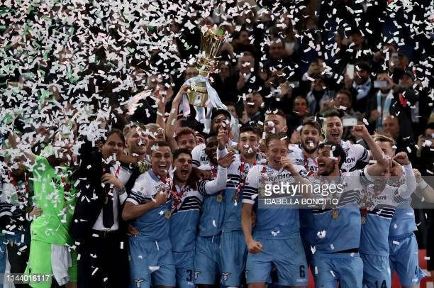 Lazio's Italian coach Simone Inzaghi and his team players celebrate as they hold the Tim Cup trophy during the trophy ceremony after winning the...