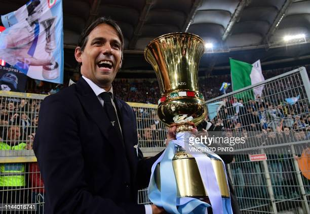 Lazio's Italian coach Simone Inzaghi celebrates as he holds the Tim Cup trophy during the trophy ceremony after winning the Coppa Italia final match...