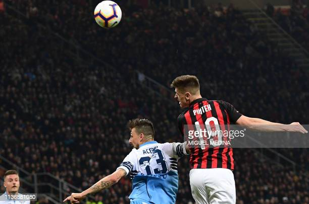 Lazio's Italian defender Francesco Acerbi and AC Milan's Polish forward Krzysztof Piatek go for a header during the Italian Serie A football match AC...