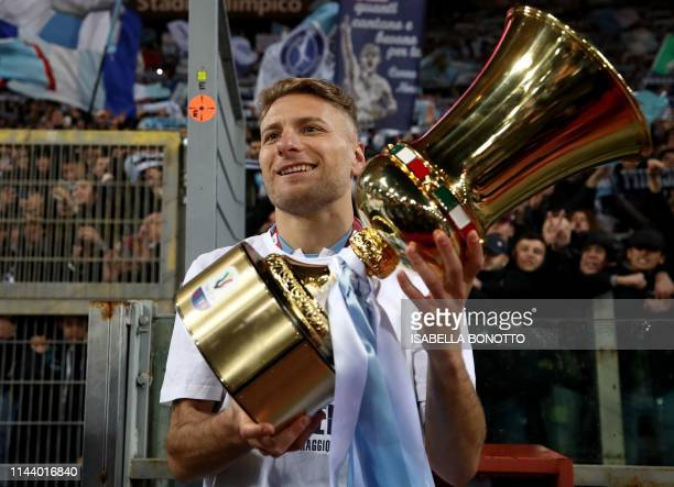 Lazio's Italian forward Ciro Immobile celebrates as he holds the Tim Cup trophy during the trophy ceremony after winning the Coppa Italia final match...