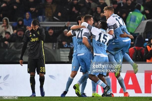 Lazio's Italian forward Ciro Immobile celebrates with his teammates as Juventus' Uruguayan midfielder Rodrigo Bentancur reacts after Juventus' scored...