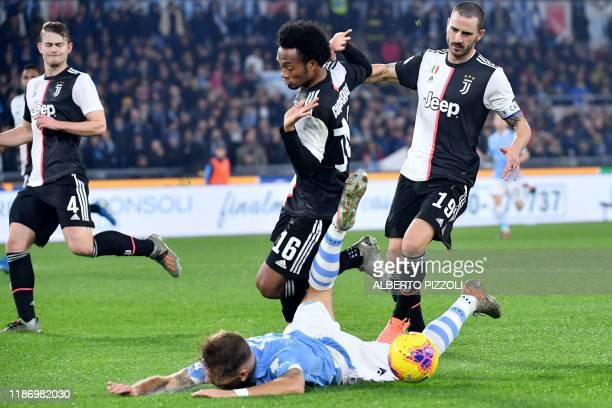 Lazio's Italian forward Ciro Immobile falls in the penalty area after colliding with Juventus' Colombian midfielder Juan Cuadrado during the Italian...