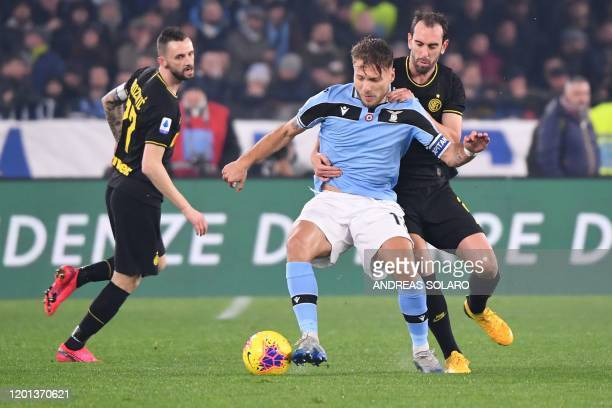 Lazio's Italian forward Ciro Immobile holds off Inter Milan's Uruguayan defender Diego Godin during the Italian Serie A football match Lazio Rome vs...