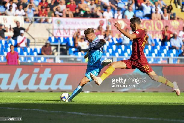 Lazio's Italian forward Ciro Immobile outruns AS Rome's Argentine defender Federico Fazio to shoot and score an equalizer during the Italian Serie A...