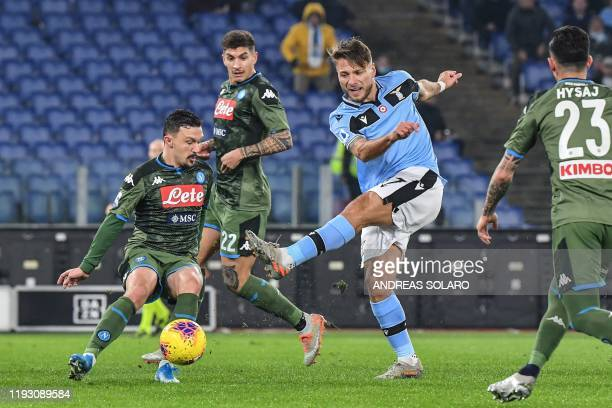 Lazio's Italian forward Ciro Immobile shoots on goal despite Napoli's Portuguese defender Mario Rui during the Italian serie A football match Lazio...