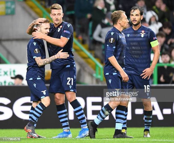 Lazio's Italian midfielder Manuel Lazzari celebrates scoring the opening goal with Lazio's Serbian midfielder Sergej MilinkovicSavic during the UEFA...