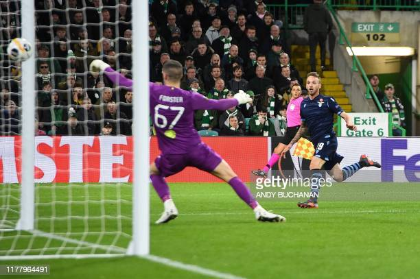 Lazio's Italian midfielder Manuel Lazzari scores the opening goal past Celtic's English goalkeeper Fraser Forster during the UEFA Europa League group...