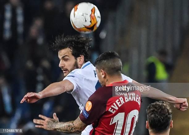 Lazio's Italian midfielder Marco Parolo and Sevilla's Argentine midfielder Ever Banega go for a header during the UEFA Europa League round of 16...