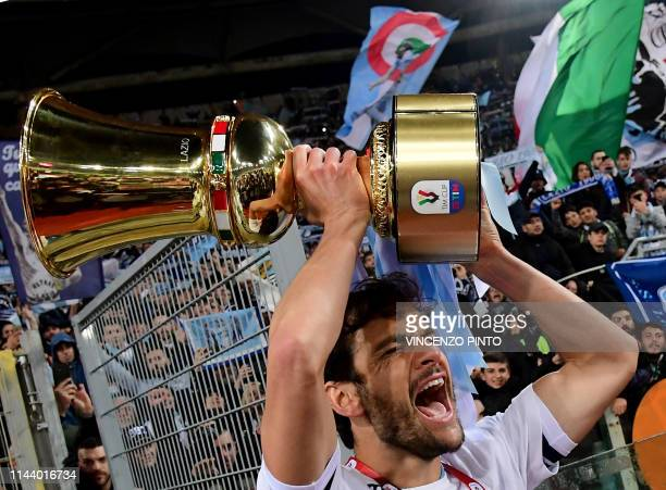 Lazio's Italian midfielder Marco Parolo celebrates as he holds the Tim Cup trophy during the trophy ceremony after winning at the end of the Coppa...