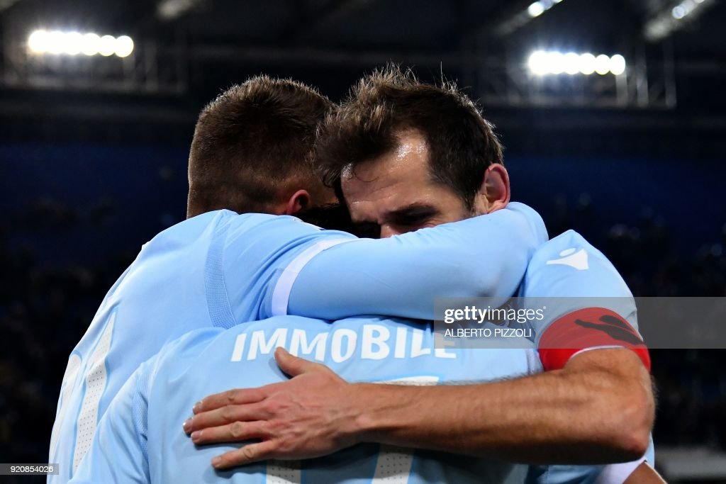 Lazio's midfielder Ciro Immobile (C - back) is congratulated by teammates after scoring during the Italian Serie A football match Lazio vs Hellas Verona on February 19, 2018 at Olympic stadium in Rome. /