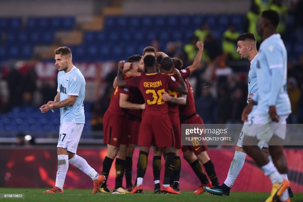 Lazio's midfielder Ciro Immobile (L) looks dejected as AS Roma's players celebrate after winning the Italian Serie A football match AS Roma vs Lazio on November 18, 2017 at the Olympic stadium in Rome. / AFP PHOTO / Filippo MONTEFORTE