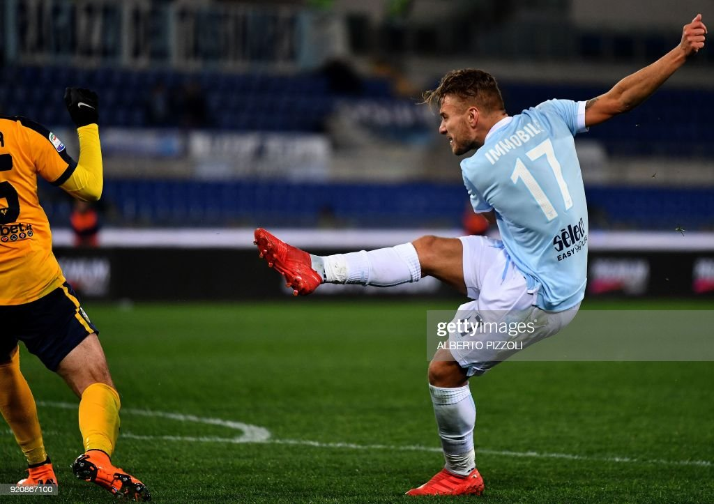 Lazio's midfielder Ciro Immobile (R) shoots and scores during the Italian Serie A football match Lazio vs Hellas Verona on February 19, 2018 at Olympic stadium in Rome. /