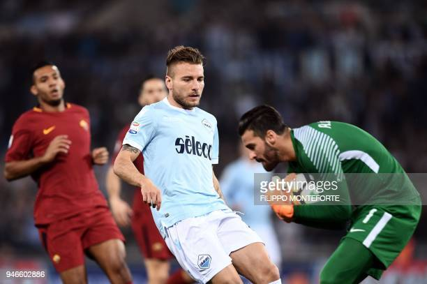 Lazio's midfielder Ciro Immobile vies for the ball with Roma's goalkeeper from Brazil Alisson Ramses Becker during the Italian Serie A football match...