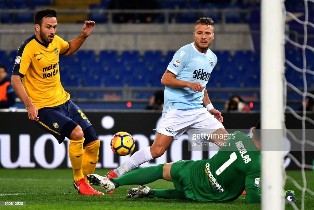 Lazio's midfielder Ciro Immobile (C) vies with Hellas Verona's defender from Uruguay Martin Caceres (L) and Hellas Verona's Brazilian goalkeeper Nicolas Andrade (R) during the Italian Serie A football match Lazio vs Hellas Verona on February 19, 2018 at Olympic stadium in Rome. /