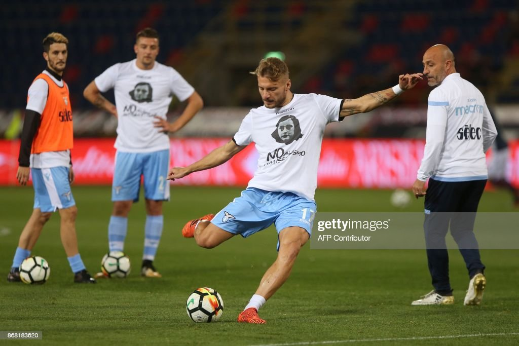 Lazio's midfielder Ciro Immobile wears a t-shirt against antisemitism showing an image of holocaust victim Anne Frank, during the warm up prior the Italian Serie A football match Bologna vs Lazio on October 25, 2017 at the Renato-Dall'Ara stadium in Bologna. Emotions were still running high in Italy, days after Lazio fans posted anti-semitic photos of Anne Frank in a Roma jersey in the stands of the Stadio Olimpico. The Italian football federation announced that there will be a minute's reflection on the Holocaust before every match and a passage read from 'The Diary of Anne Frank'. At the same time referees and captains will hand out copies of the diary and Italian Jewish writer Primo Levi's memoir 'If This Is A Man'. PHOTO / Gianni SCHICCHI