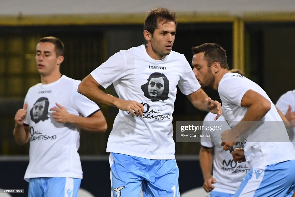Lazio's midfielder from Bosnia-Herzegovina Senad Lulic (C) and teammates wear t-shirts against antisemitism showing an image of holocaust victim Anne Frank, during the warm up prior the Italian Serie A football match Bologna vs Lazio on October 25, 2017 at the Renato-Dall'Ara stadium in Bologna. Emotions were still running high in Italy, days after Lazio fans posted anti-semitic photos of Anne Frank in a Roma jersey in the stands of the Stadio Olimpico. The Italian football federation announced that there will be a minute's reflection on the Holocaust before every match and a passage read from 'The Diary of Anne Frank'. At the same time referees and captains will hand out copies of the diary and Italian Jewish writer Primo Levi's memoir 'If This Is A Man'. PHOTO / Gianni SCHICCHI