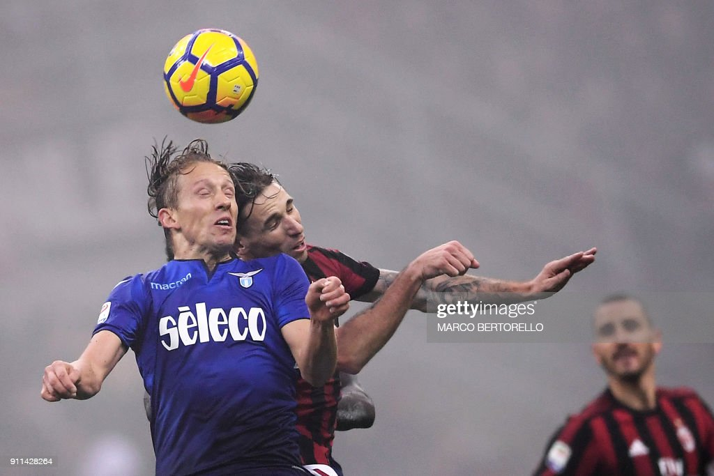 Lazio's midfielder Lucas Leiva Pezzini from Brazil (L) fights for the ball with AC Milan's midfielder Lucas Biglia from Argentina (C) during the Italian Serie A football match AC Milan Vs Lazio on January 28, 2018 at the 'Giuseppe Meazza' Stadium in Milan. /