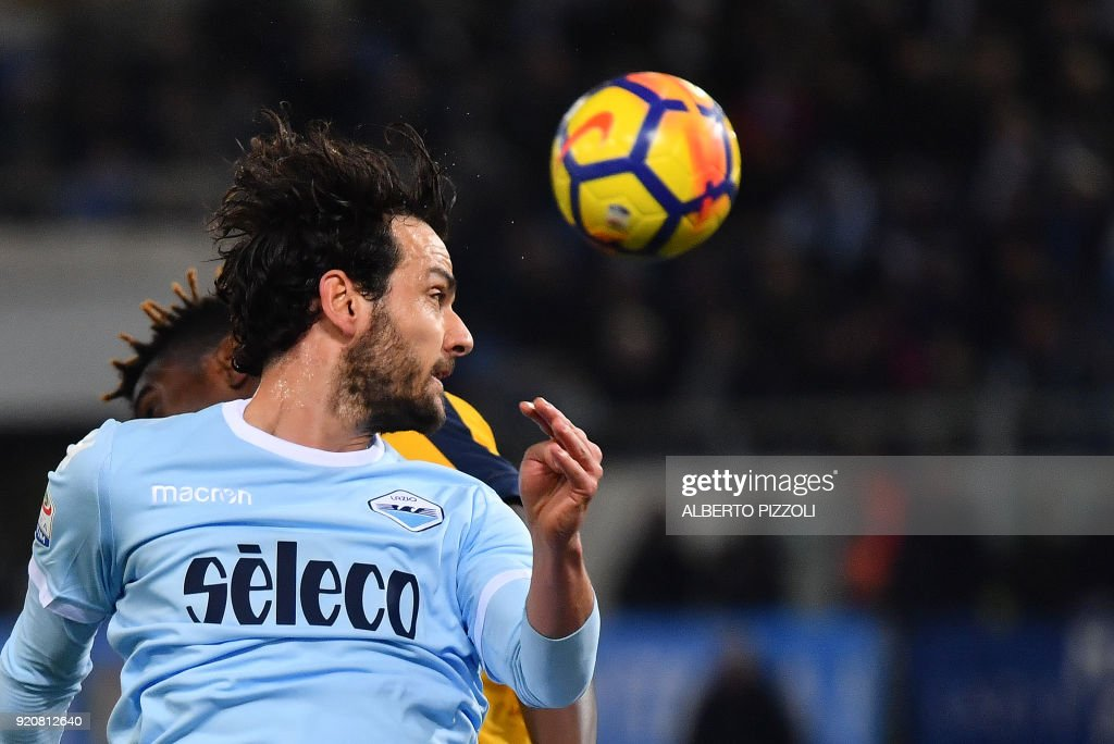 Lazio's midfielder Marco Parolo (front) heads the ball during the Italian Serie A football match Lazio vs Hellas Verona on February 19, 2018 at Olympic stadium in Rome. /