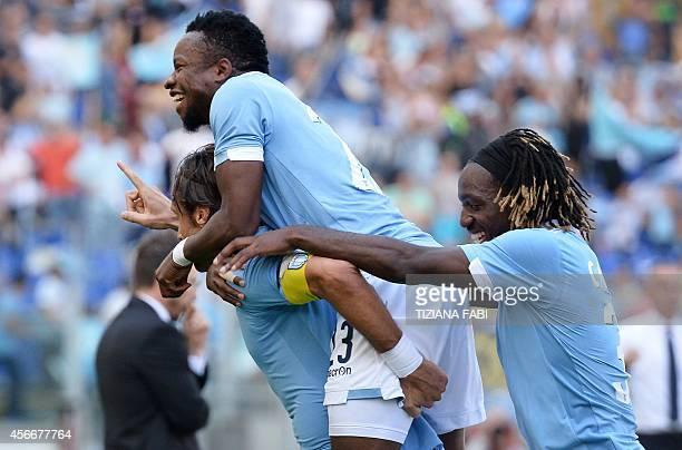Lazio's midfielder Stefano Mauri celebrates with teammates Lazio's midfielder from Nigeria Ogenyi Onazi and Lazio's midfielder Danilo Cataldi after...