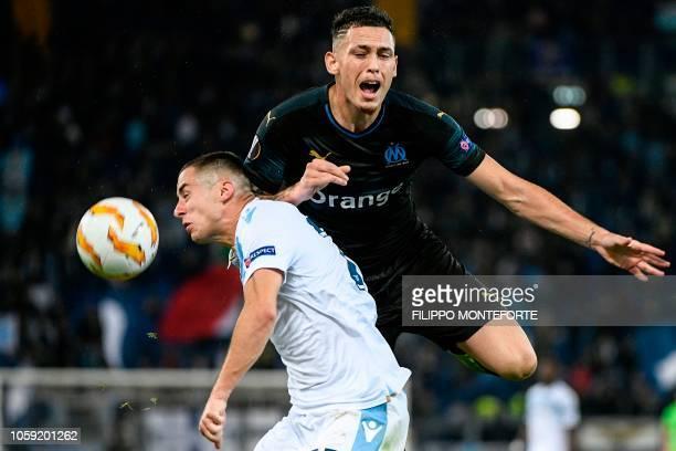 Lazio's Montenegrin midfielder Adam Marusic and Marseille's Argentine midfielder Lucas Ocampos go for a header during the UEFA Europa League group H...