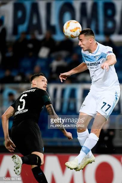 Lazio's Montenegrin midfielder Adam Marusic heads the ball next to Marseille's Argentine midfielder Lucas Ocampos during the UEFA Europa League group...