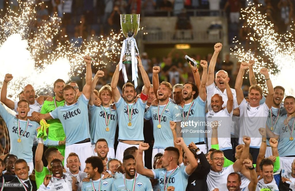 Lazio's players celebrate with the trophy after winning the Italian SuperCup TIM football match Juventus vs lazio on August 13, 2017 at the Olympic stadium in Rome. / AFP PHOTO / Alberto PIZZOLI