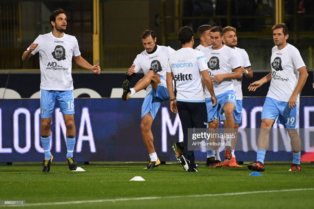 Lazio's players wearing t-shirts against antisemitism showing an image of holocaust victim Anne Frank, warm up prior the Italian Serie A football match Bologna vs Lazio on October 25, 2017 at the Renato-Dall'Ara stadium in Bologna. Emotions were still running high in Italy, days after Lazio fans posted anti-semitic photos of Anne Frank in a Roma jersey in the stands of the Stadio Olimpico. The Italian football federation announced that there will be a minute's reflection on the Holocaust before every match and a passage read from 'The Diary of Anne Frank'. At the same time referees and captains will hand out copies of the diary and Italian Jewish writer Primo Levi's memoir 'If This Is A Man'. PHOTO / Gianni SCHICCHI