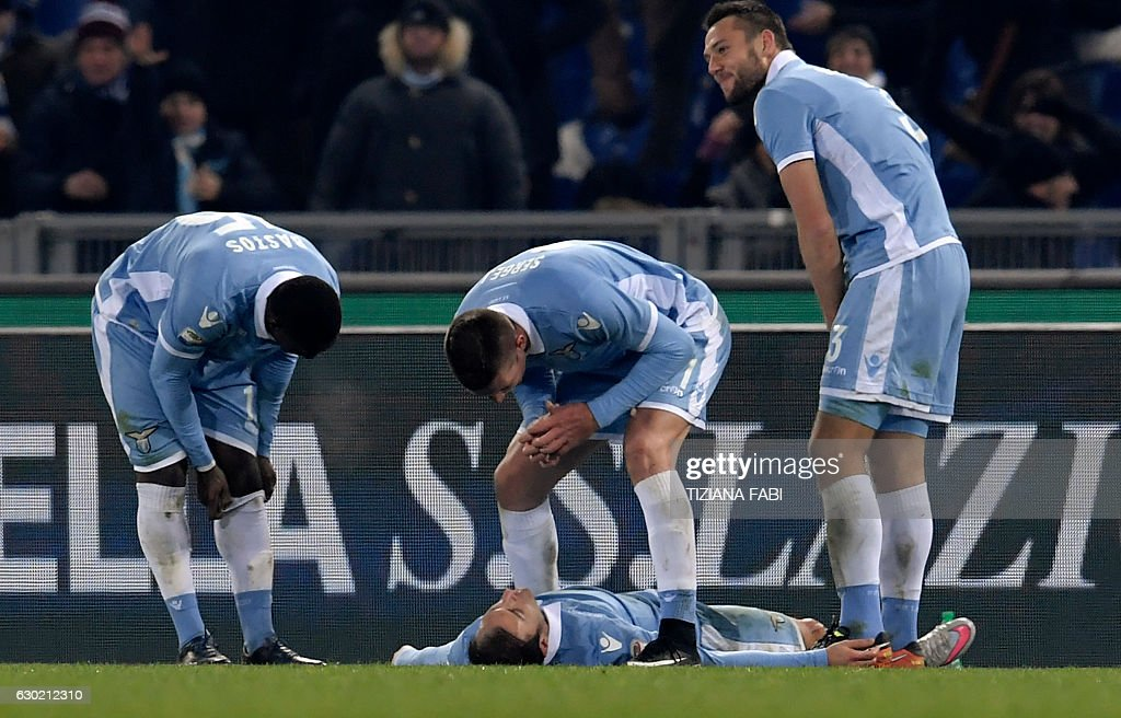 Lazio's Romanian defender Stefan Radu (on the ground) celebrates with teammates after scoring a goal during the Serie A football match between Lazio and Fiorentina at Olympic Stadium in Rome on December 18, 2016. / AFP / TIZIANA