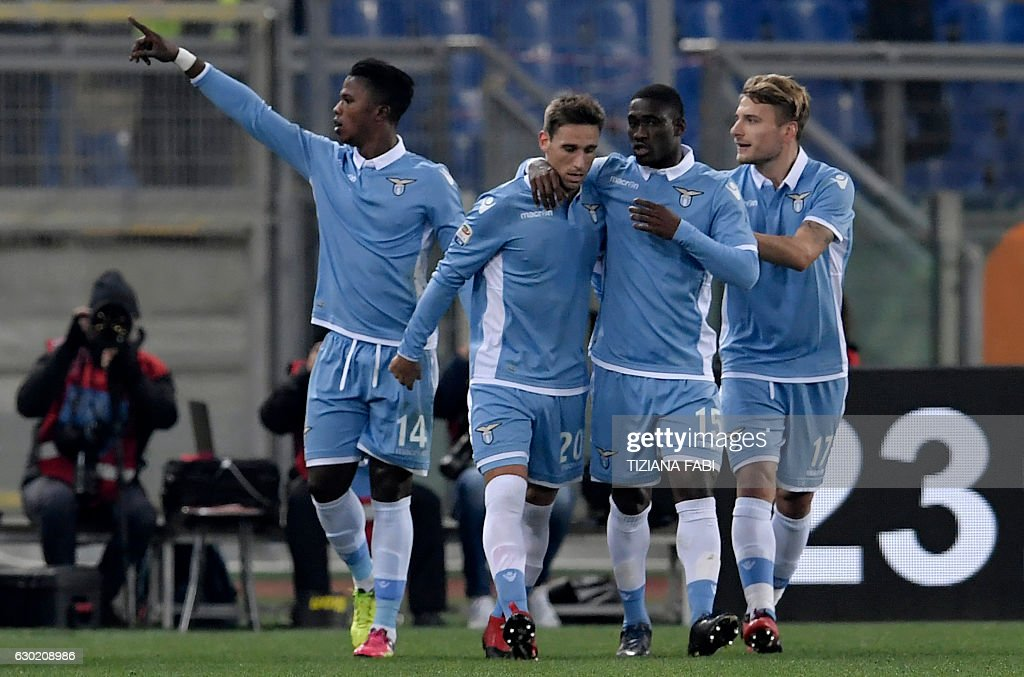 Lazio's Senegalese forward Balde Diao Keita (L) celebrates with teammates after scoring a goal during the Serie A football match between Lazio and Fiorentina at Olympic Stadium in Rome on December 18, 2016. / AFP / TIZIANA