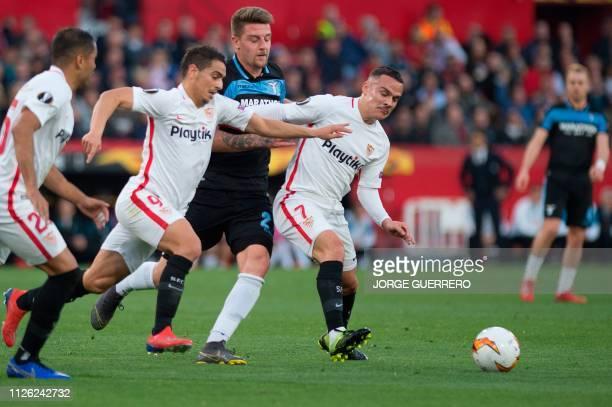 Lazio's Serbian midfielder Sergej MilinkovicSavic fights for the ball with Sevilla's French forward Ben Yedder and Spanish midfielder Roque Mesa...