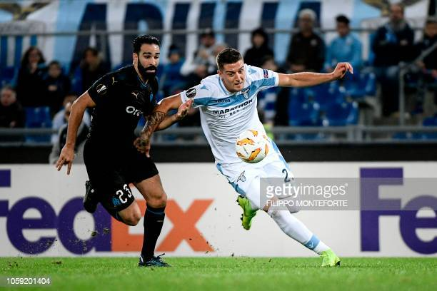 Lazio's Serbian midfielder Sergej MilinkovicSavic outruns Marseille's French defender Adil Rami during the UEFA Europa League group H football match...