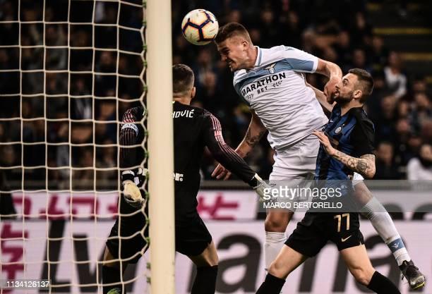 Lazio's Serbian midfielder Sergej MilinkovicSavic scores a header past Inter Milan's Slovenian goalkeeper Samir Handanovic despite Inter Milan's...