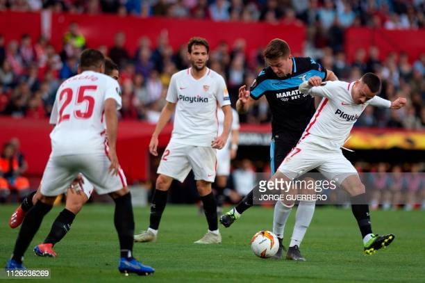 Lazio's Serbian midfielder Sergej MilinkovicSavic vies for the ball with Sevilla's Spanish midfielder Roque Mesa during the UEFA Europa League round...