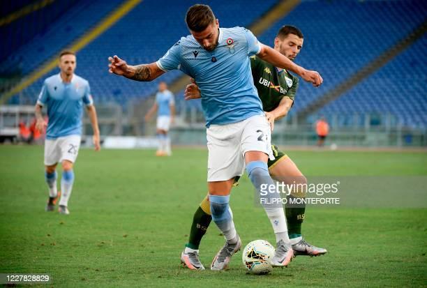 Lazio's Serbian midfielder Sergej MilinkovicSavic vies with Brescia's Italian defender Daniele Gastaldello during the Serie A football match Lazio vs...