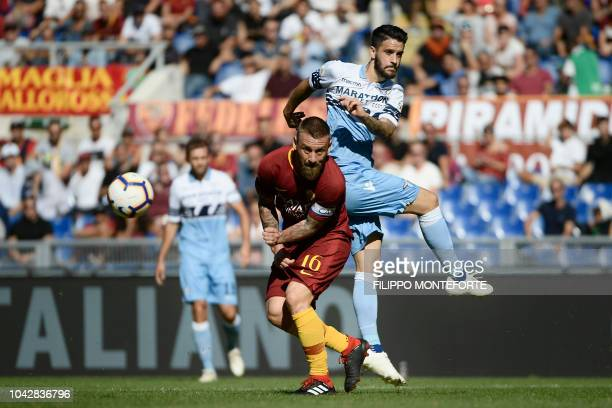 TOPSHOT Lazio's Spanish midfielder Luis Alberto and AS Rome's Italian midfielder Daniele De Rossi go for the ball during the Italian Serie A football...