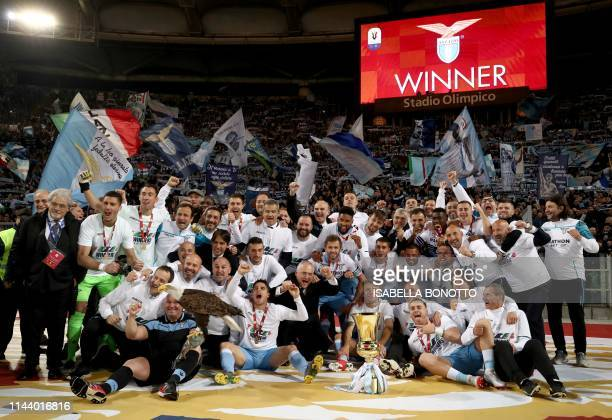 Lazio's team players and members of staff celebrate as they hold the Tim Cup trophy during the trophy ceremony after winning the Coppa Italia final...