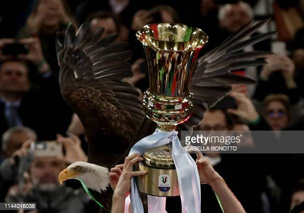 Lazio's team players holds the Tim Cup trophy with the mascot eagle on the background during the trophy ceremony after winning the Coppa Italia final...