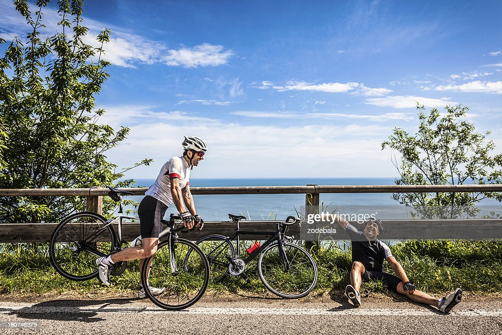Lazy Cyclist Resting on the Road During a Bike Race : Stock Photo