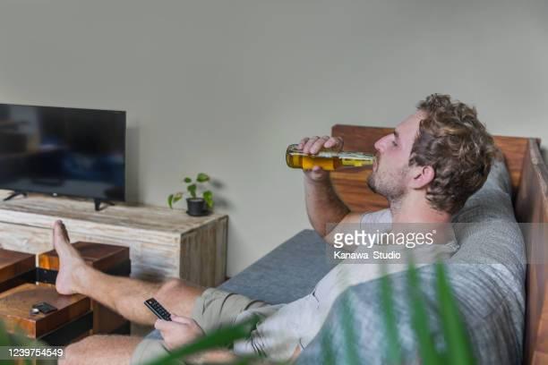 fauler mann genießen filmabend allein - corona beer stock-fotos und bilder